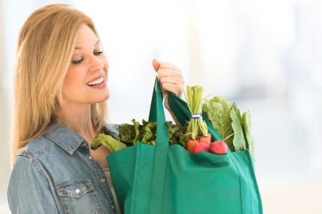 Happy mature woman carrying shopping bag full of vegetables. She is smiling at home. Female is showing her fit and healthy lifestyle.